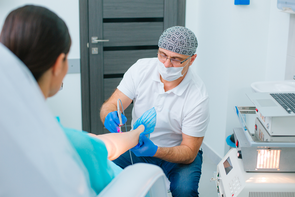 Skilled doctor using lasers to treat small veins on the leg