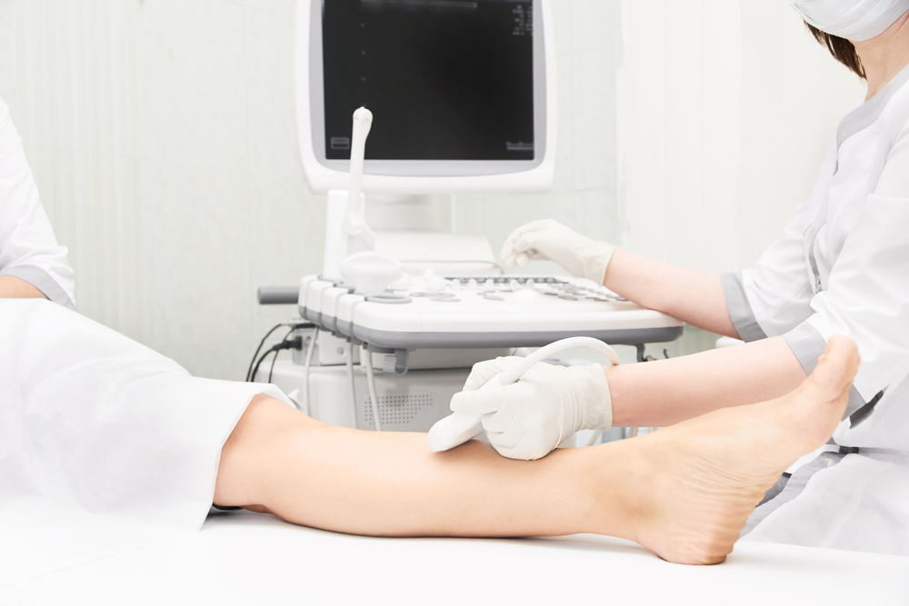 Doctor assistant doing patient ultrasound of leg